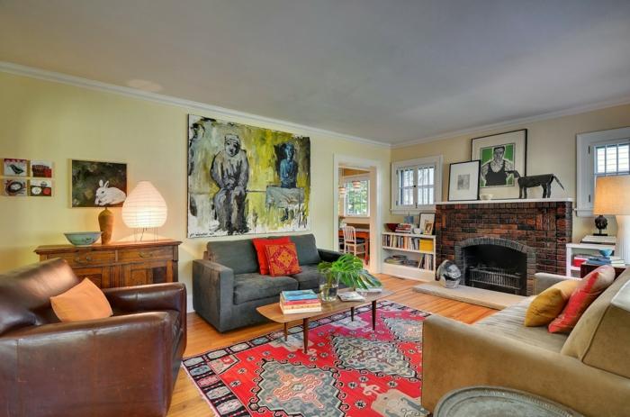 tapis coloré aux éléments ethniques, grands canapés en style différent, peinture murale abstraite, cheminée en briques