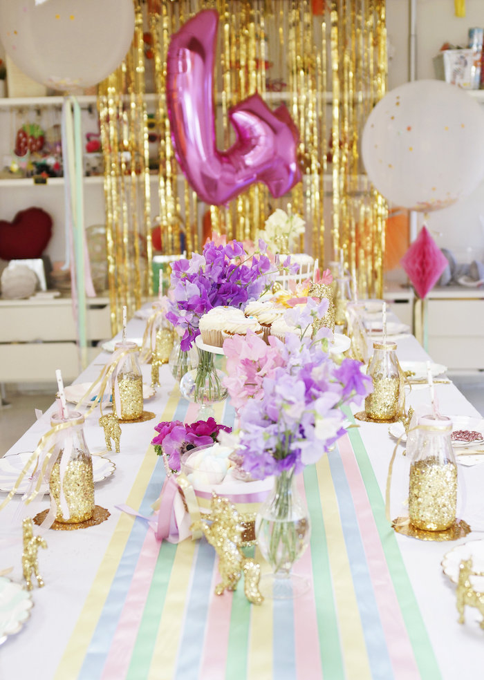 décoration de table girly en couleurs pastel et doré sur le theme licorne avec une superposition de nappe blanche et un chemin de table rayé