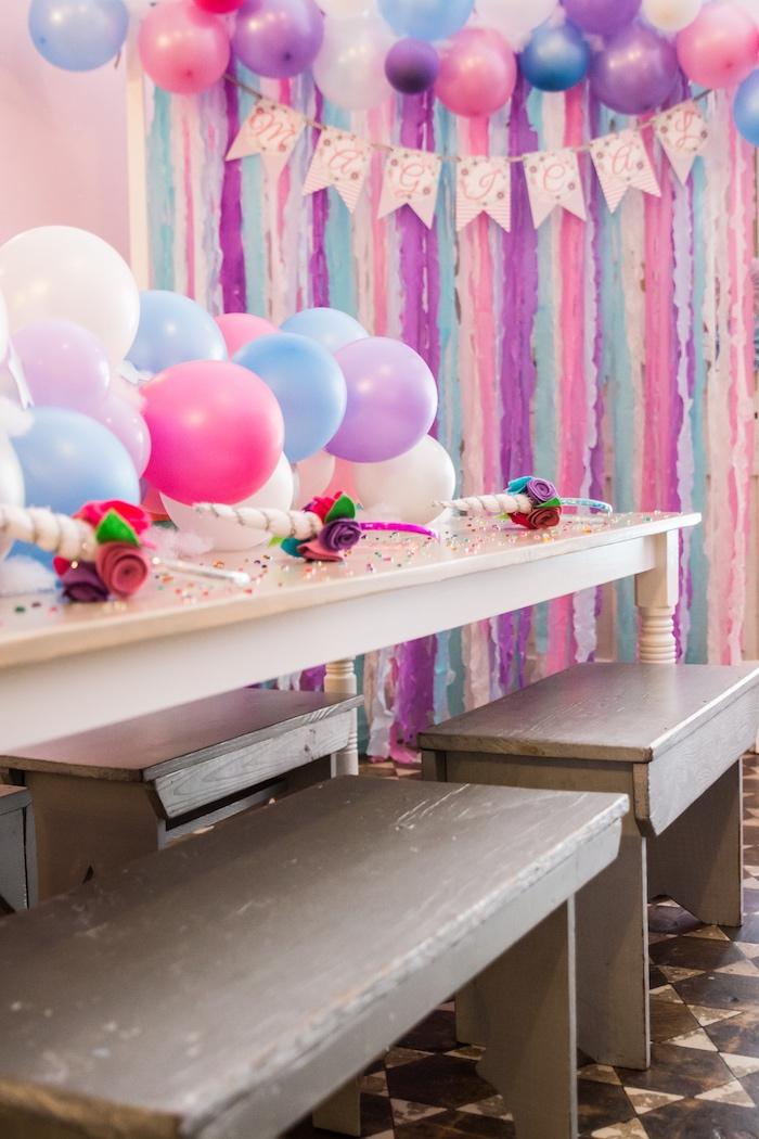 idées déco pour un anniversaire licorne, un chemin de table original en ballons aux couleurs du rideau à franges