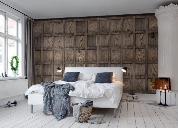 aménagement de chambre à coucher blanc et bois avec revêtement mural en papier peint imitation bois et cheminée blanche