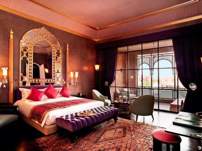 grande fenêtre style atelier, miroir encadré de couleur or, trois coussins rougesn banquette lilas, tapis ethnique, plafond rose