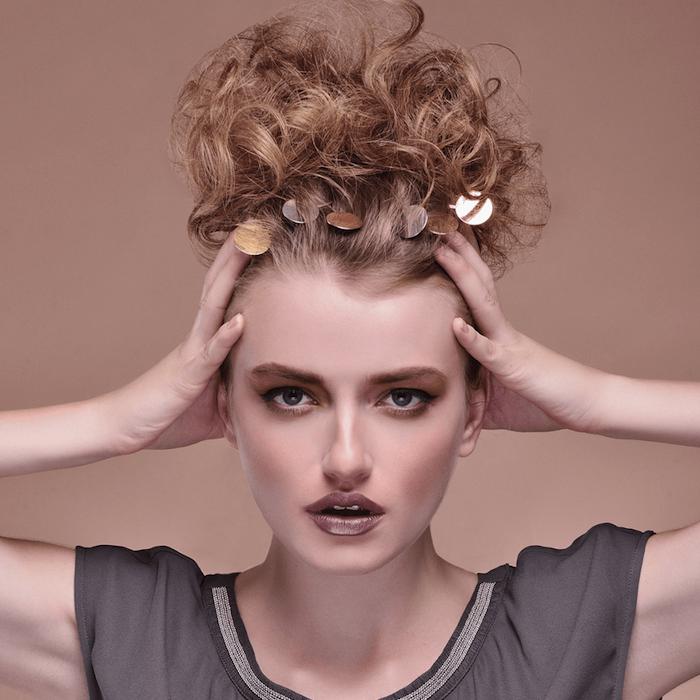 boucle cheveux femme en chignon décoiffé hait, cheveux attachés en haut, maquillage marron, chemise grise, accessoire cheveux doré