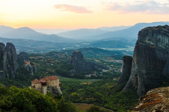 photo de site touristique les Météores en Grèce, vue d'en haut vers les montagnes lointaines et le village au lever du soleil