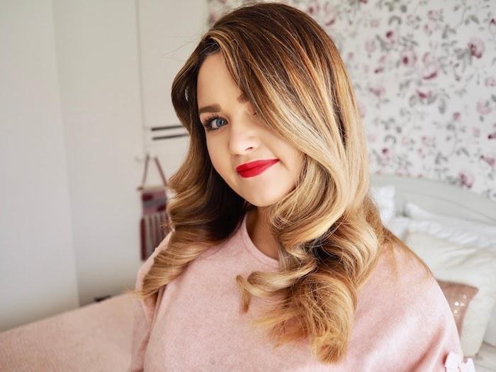 idée de coiffure cheveux ondulés femme racines chatain foncé et longieurs blond foncé, rouge à lèvres rouge, pull femme rose