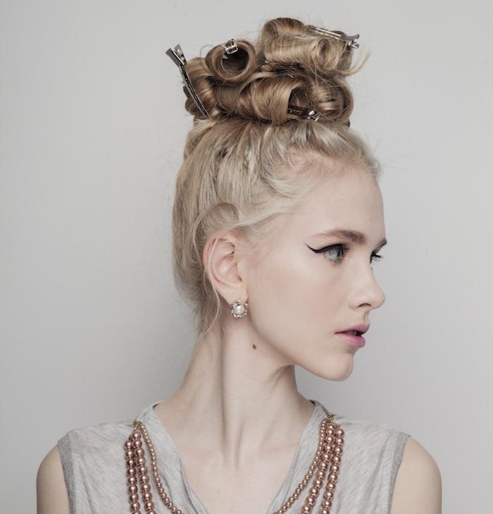 cheveux bouclés femme, coiffure chignon haut de gros boucles en haut de la tête accessoirisés avec de sépingles à cheveux, quelques mèches rebelles