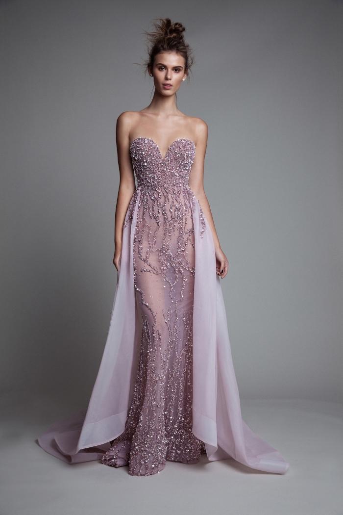 femme avec robe soirée longue transparente de nuance rose pâle avec bustier en forme de coeur et volants