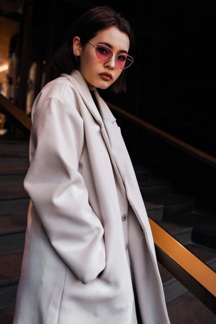 coiffure courte ultra tendance avec un carré brun au tracé net et précis accessoirisé avec une paire de lunettes verre coloré