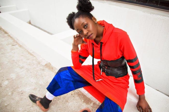 cheveux frisés femme avec une coiffure macarons sur cheveux noirs crépus, idée de coiffure afro femme, street style, tenue de sport chic