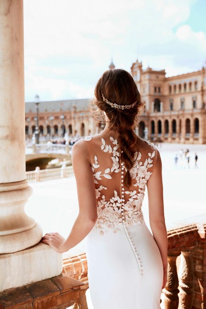 vision romantique avec coiffure en tresse et couronne, modèle de robe de mariée blanche à dos boutonné avec fleurs