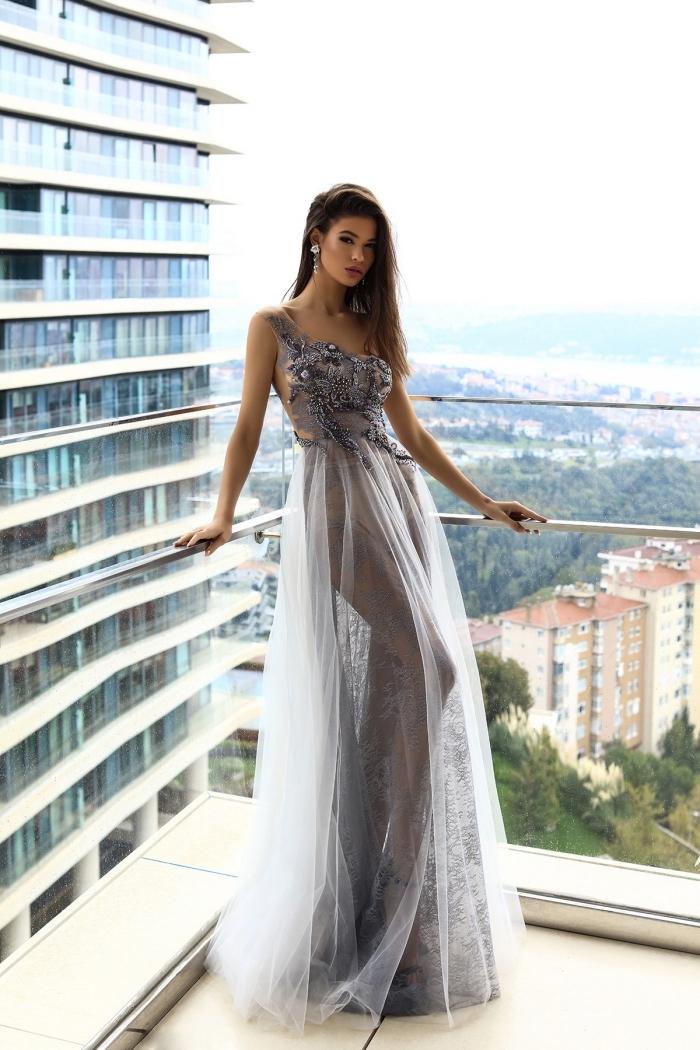 exemple de robe princesse avec jupe à volants en tulle gris clair et haut à col asymétrique avec décoration florale