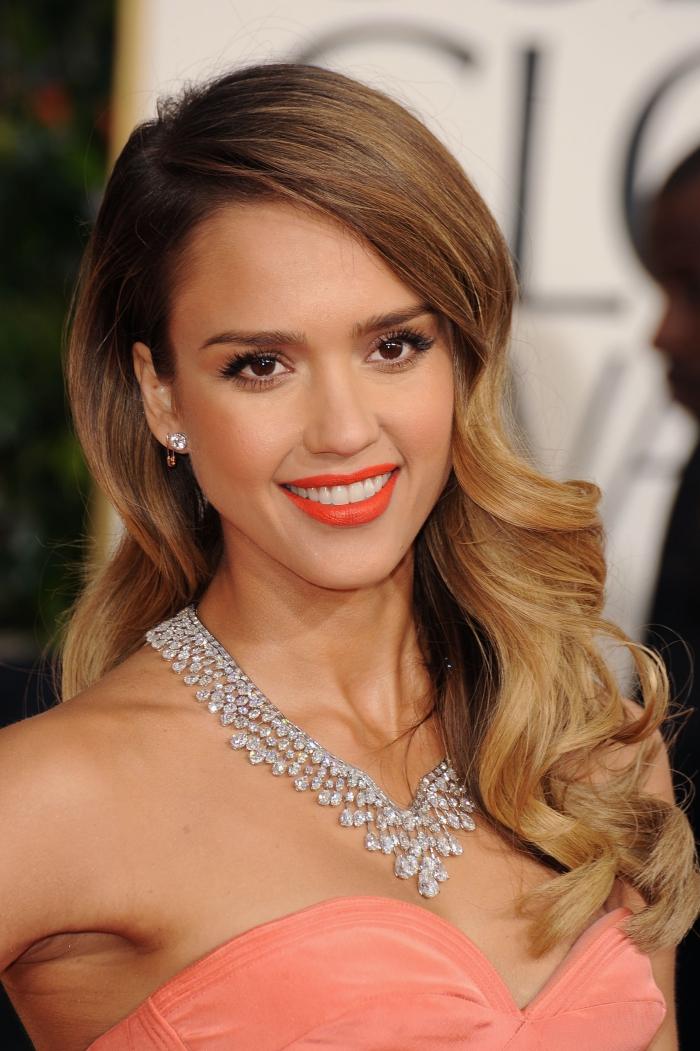 coiffure célébrité de Jessica Alba aux cheveux ombré naturellement bouclés de côté, bijoux élégants et féminins en diamants
