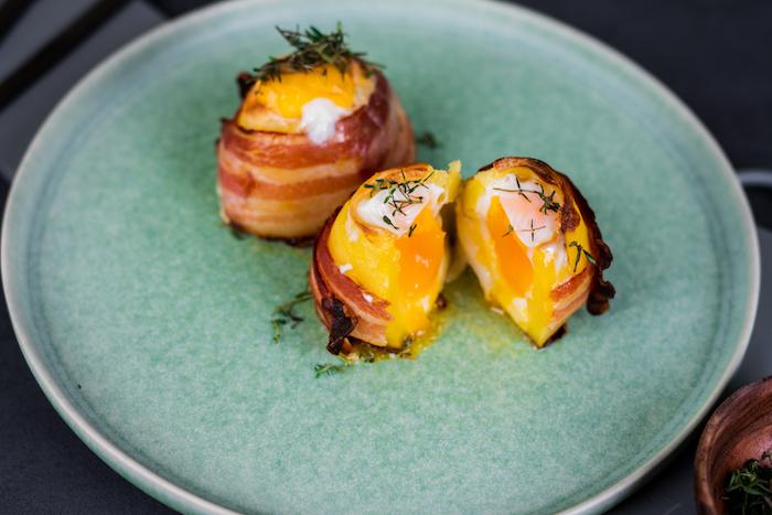 recette repas du soir léger constitué de pommes de terre farcies avec oeuf et fromage cheddar, bande de bacon pour envelopper