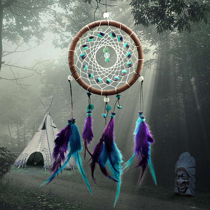 comment fabriquer un attrape reve, cercle marron, filet blanc, perles décoratives bleues et noires, plumes déco en bleu et violet, fond forêt, tente indienne