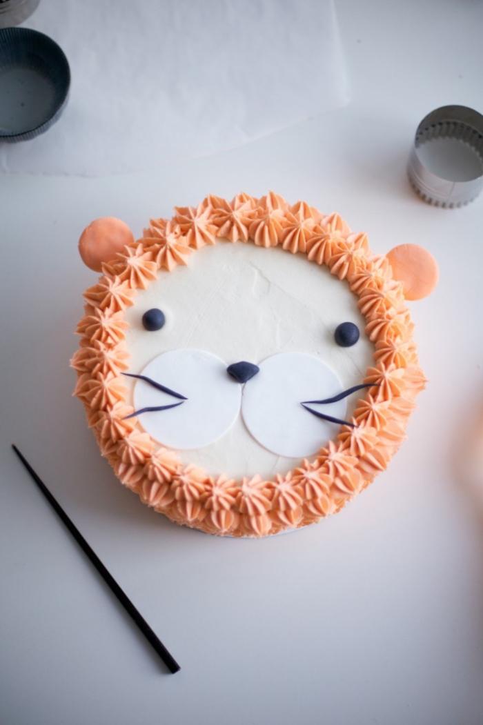 tuto pour faire une décoration gateau anniversaire personnalisé façon tête de lion, crinière en lion réalisées au glaçage orange