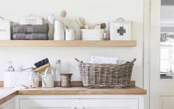 objets de nettoyage et produits ménagers arrangés sur une étagère de bois clair au-dessus d'un plan de travaux en bois