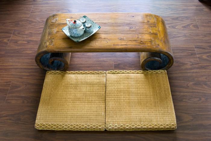 feng shui salon, parquet en couleur cerise, table basse en bois clair avec es bouts arrondis, deux couvertures sur le sol en style zen pour deux personnes