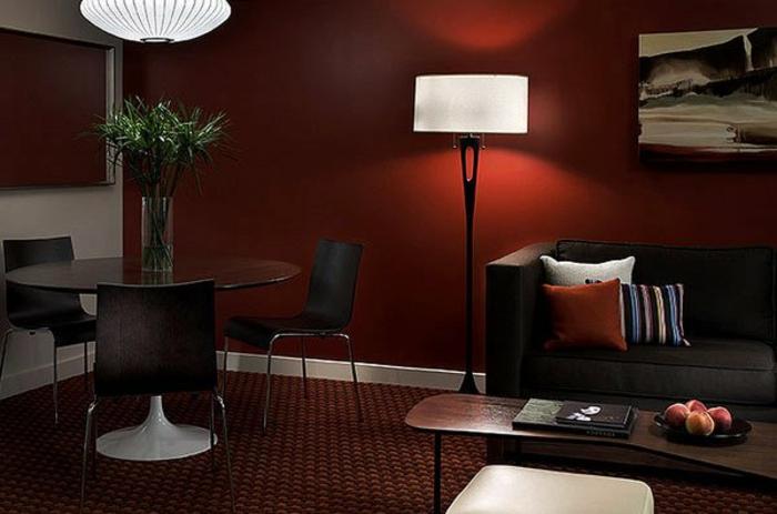 tapis moquet, table ronde en verre, table basse en bois, peinture murale couleur lie de vin