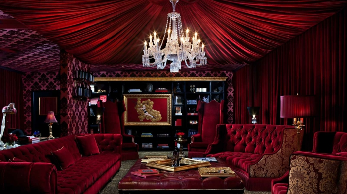 un séjour de luxe en couleu lie de vin, plafonnier cristal, sofas burgundi, rideaux