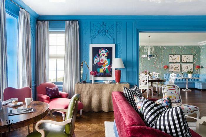 salle de séjour avec couleurs contrastantes, sofas rouges, chaises ancienne; table ovale, coussins motifs carrés