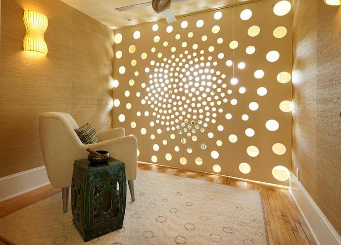 ambiance zen avec un panneaux aux motifs ajourés, type de spirale qui s'ouvre, tapis en couleur crème, fauteuil couleur crème, parquet jaune