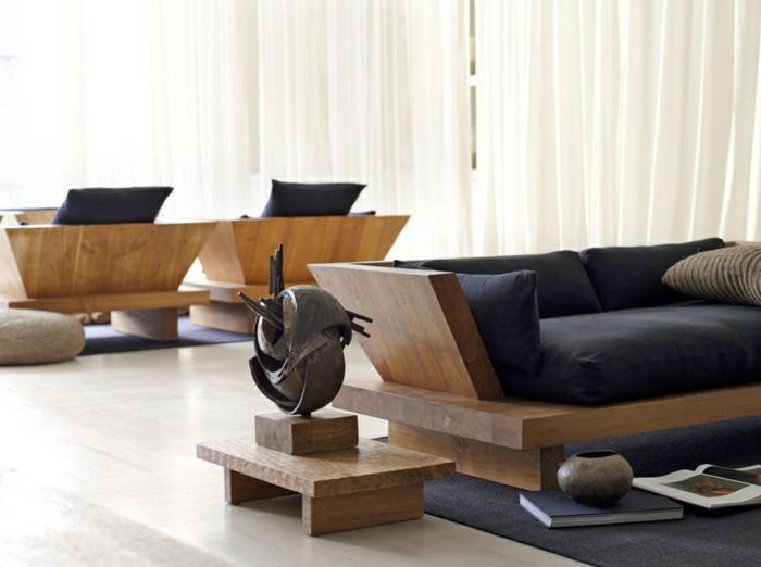 salon feng shui, deco salon zen, meubles en bois massif avec des grands coussins noirs, statuette en bronze et bois posé sur un petit piédestal en bois, tapis en gris anthracite