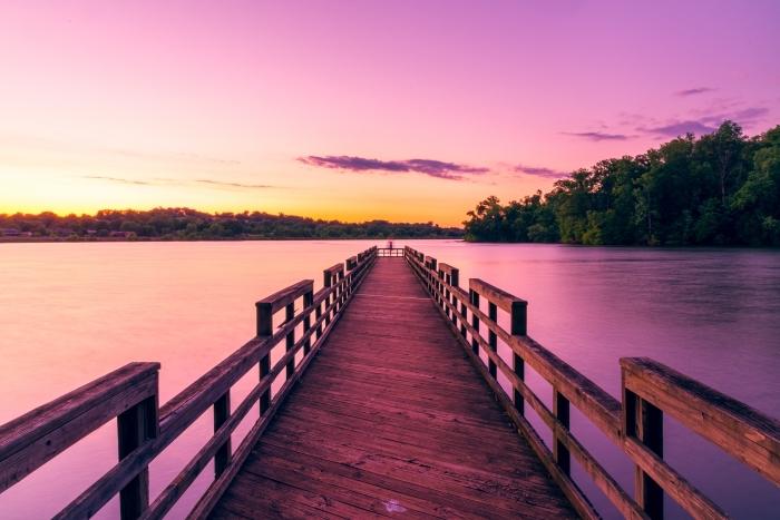 pont de bois au-dessus d'un lac avec forêt d'arbre et ciel en couleurs rose et jaune illuminé par les rayons du soleil, wallpaper fond d écran lever du soleil