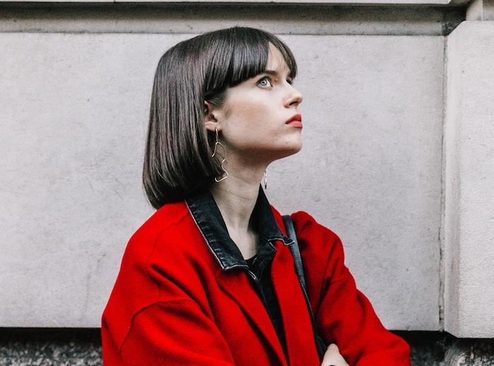 coupe de cheveux femme court, carré drout chatain foncé avec frange sur le front façon rideaux, manteau femme rouge