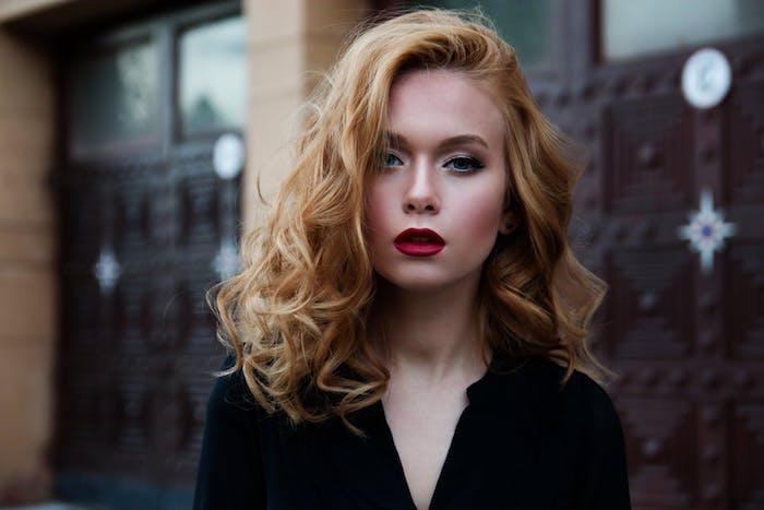 exemple de coiffure cheveux bouclés ondulations fines sur cheveux blond cuivré avec mèche sur le coté et tailleur femme noir