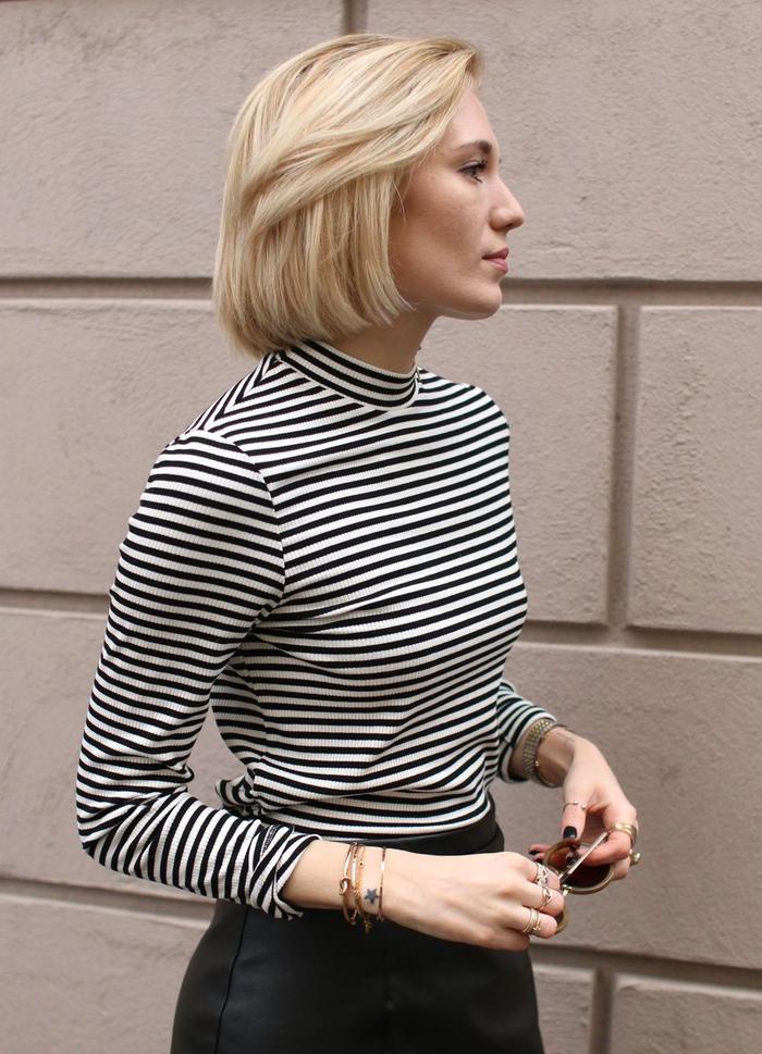 une coupe mi courte femme aux allures classique, carré blond et lisse avec une frange de côté