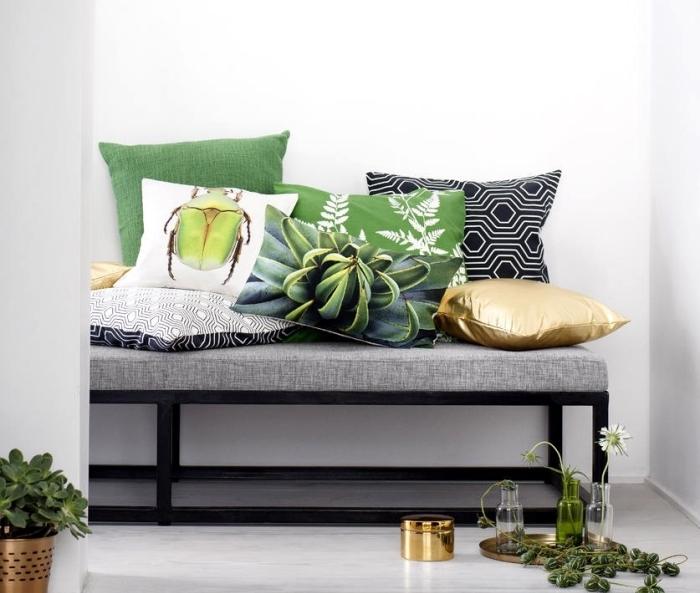 idée pour la deco couloir aux murs blancs avec banc gris et noir décoré avec coussins à design tropical et or