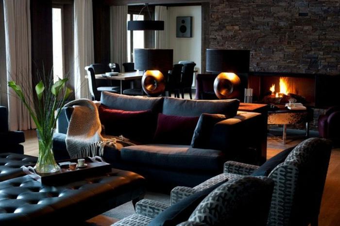 séjour couleur marsala, sofas gris, table basse capitonnée, mur en pierre apparente