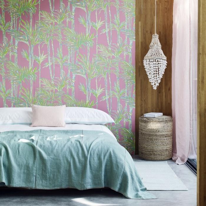 modèle de papier peint tropical en vert et rose dans une chambre à coucher aménagée avec un grand lit sur plancher de béton