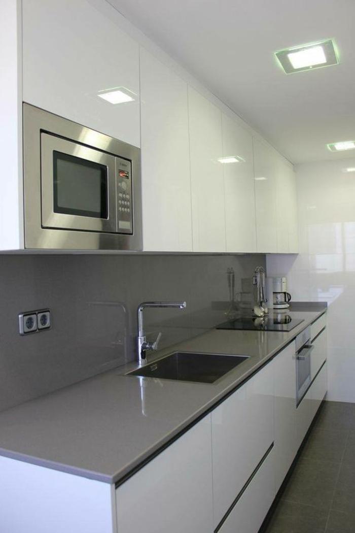 cuisine aménagée pas cher, carrelage gris brillant, four micro-ondes inséré dans un meuble de rangement suspendu blanc , plan de travail en gris perle, plafond blanc brillant avec des spots lumineux en forme carrée