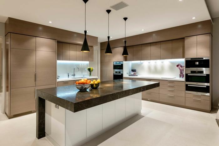 cuisine blanc et beige, îlot noir, rangement blanc, fours encastréz muraux, trois lampes noires