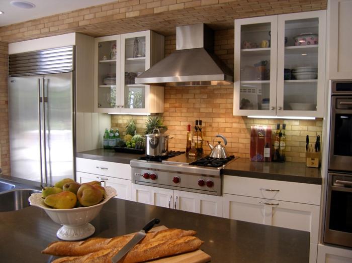 cuisine équipée avec un mur en briques rouges, placards blancs, cabinets avec portes vitrées