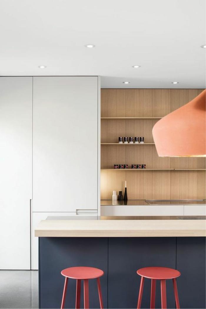espace aménagé dans un esprit minimaliste, deux tabourets en rose, ilot en bleu canard et blanc, mur avec des étagères en beige, grand luminaire moderne en couleur saumon