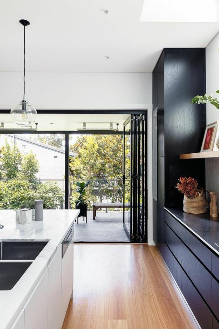 cuisine équipée ikea, parquet brillant en couleur beige nuances jaunes, meubles de rangement en noir, finition surface lisse et brillante, verrière balcon en métal noir