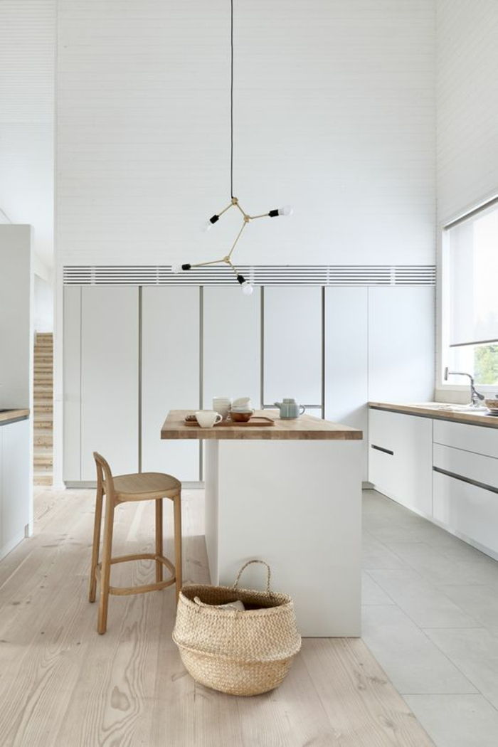 cuisine équipée moderne, cuisine blanche plan de travail bois, luminaire suspendu en métal noir, avec quatre ampoules nues, cuisine ilot en blanc et plan de travail en bois clair