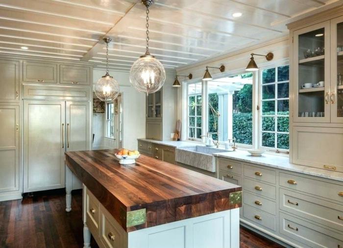 comptoir en bois avec rangement, tirois, placards et meubles blancs, sol bois foncé