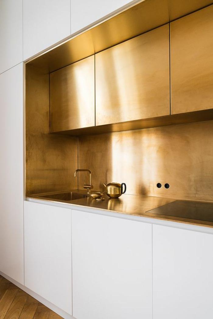 cuisine laquée blanche, avec des éléments en couleur or luisant, parquet non poli, meubles sans poignées, évier en couleur or