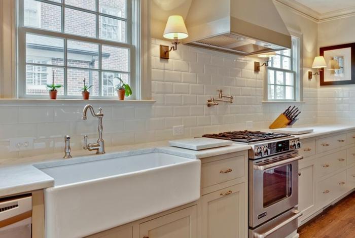 modele cuisine blanche, carrelage métro blanc, sol en bois, deux appliques murales, cuisine lumineuse