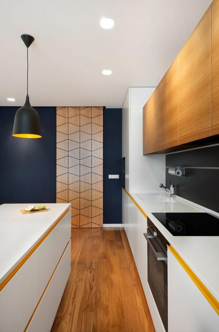 cuisine laquée blanche avec des zones en bleu canard et des lignes jaunes, parquet en jaune et nuances marrons, luminaire en bleu canard en style industriel, panneau décoratif en surface imitation bois avec des motifs graphiques losanges stylés