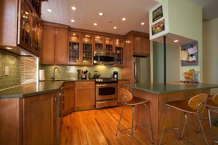 cuisine complète avec electromenager, sol en bois, chaises scandinaves, mur avec rangement en bois