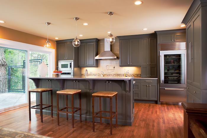 grande cuisine repeinte en gris ouverte sur sol parquet en bois foncé