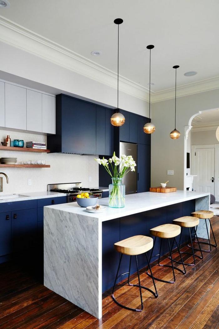 cuisine en blanc et bleu, petits tabourets de bois, sol en bois, mur avec rangement élégant