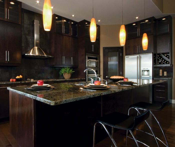 cuisine équipée avec electromenager, îlot en granit, lampes suspendues, rangement de vin, placards foncés