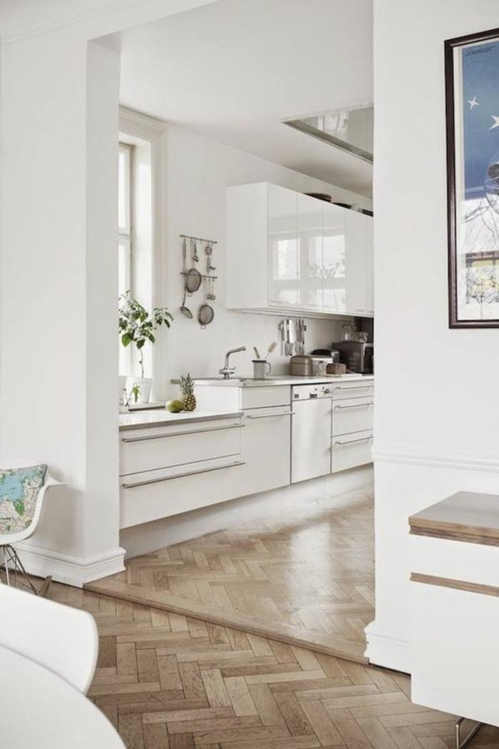cuisine aménagée pas cher, parquet en marron et jaune, meubles surface brillante, tableau avec cadre noir fin, avec image en bleu et blanc, meuble avec des pieds en métal couleur argent