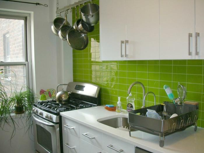cuisine blanc laqué, cuisine équipée moderne, mur au carrelage brillant en vert franc, meubles blancs et fourneaux en inox