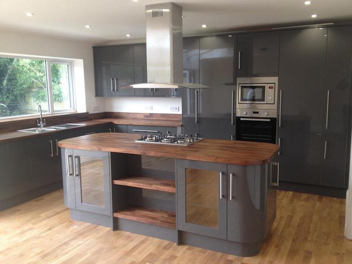 cuisine moderne équipé avec meubles encastrés gris anthracite laqués et hote centrale