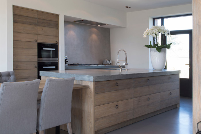 cuisine uverte avec mur finition béton et ilot central style bois sur sol gris